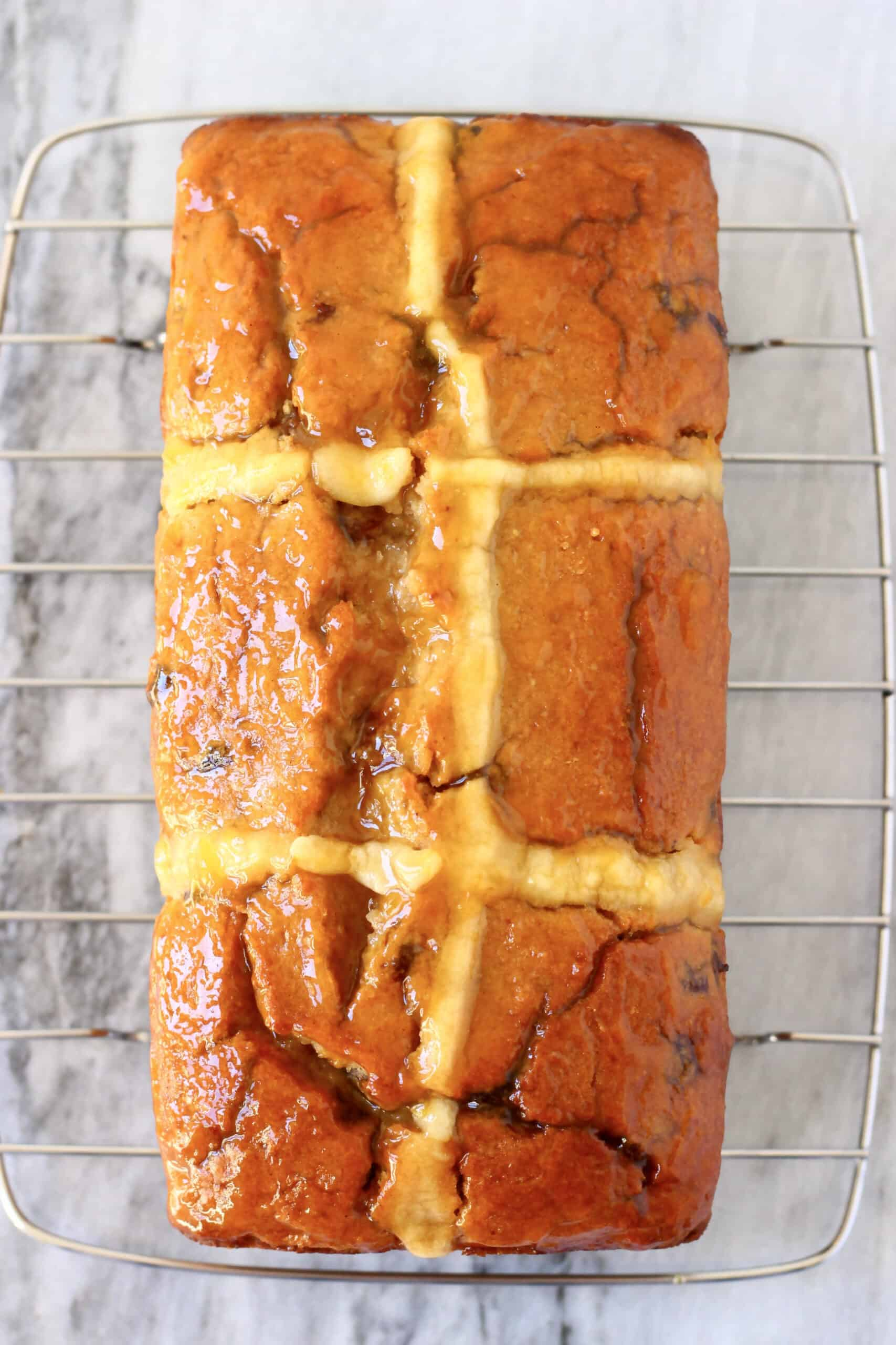 A gluten-free vegan hot cross bun loaf spread with apricot jam on a wire rack