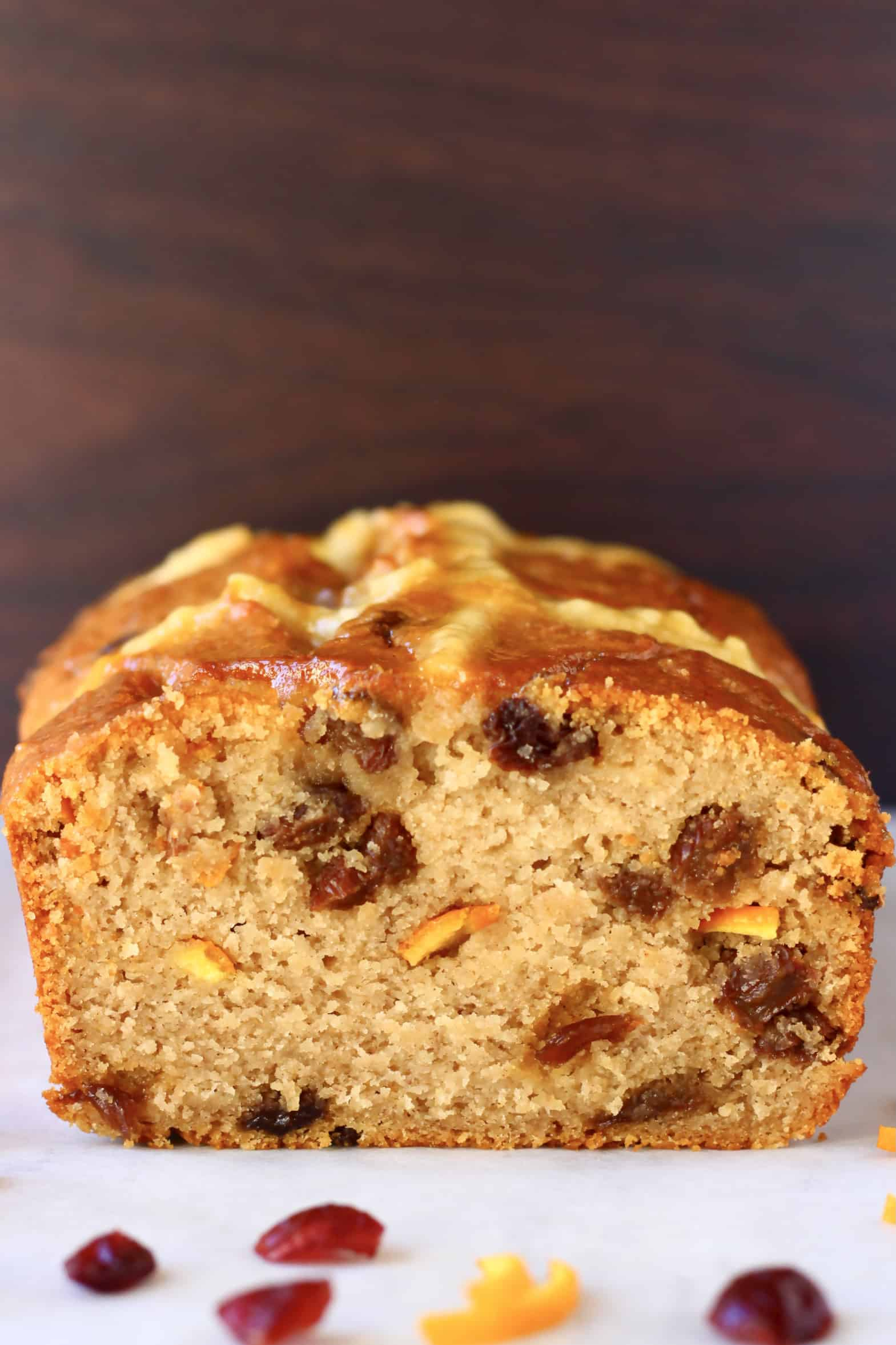 A sliced gluten-free vegan hot cross bun loaf with raisins and orange peel