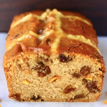 A sliced gluten-free vegan hot cross bun loaf with raisins and orange peel