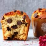Two chocolate chip muffins in brown muffin cases on a marble slab against a grey background
