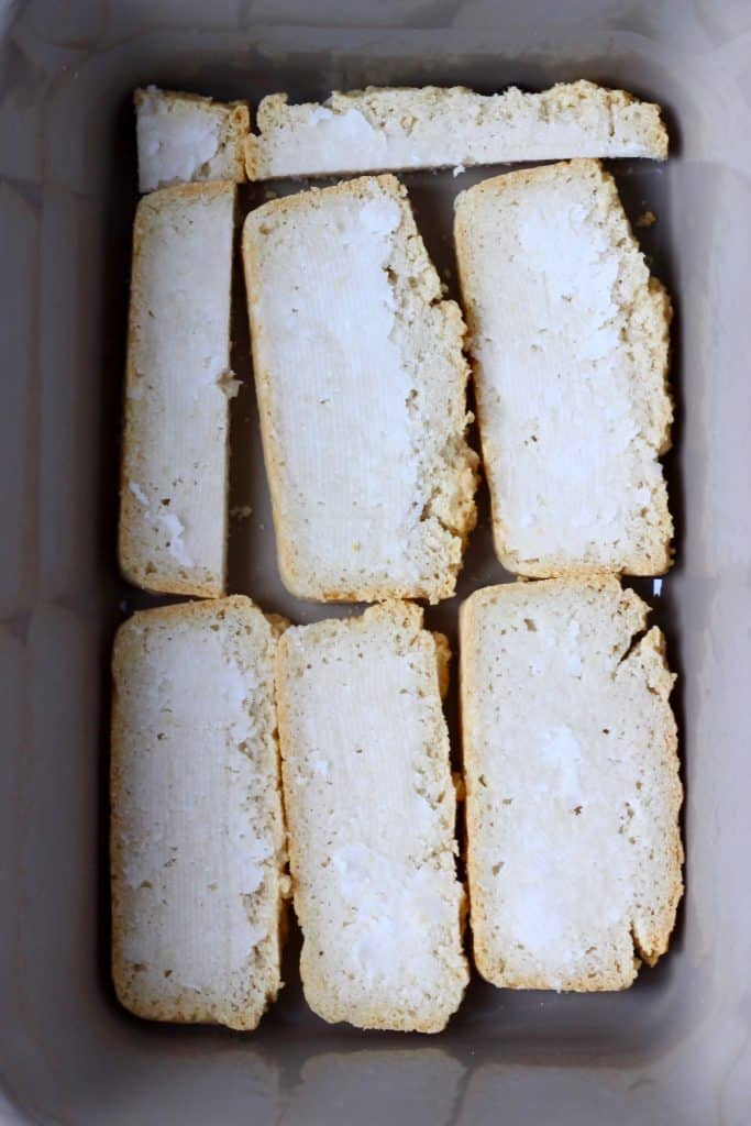 Slices of bread spread with coconut oil in a grey rectangular baking dish