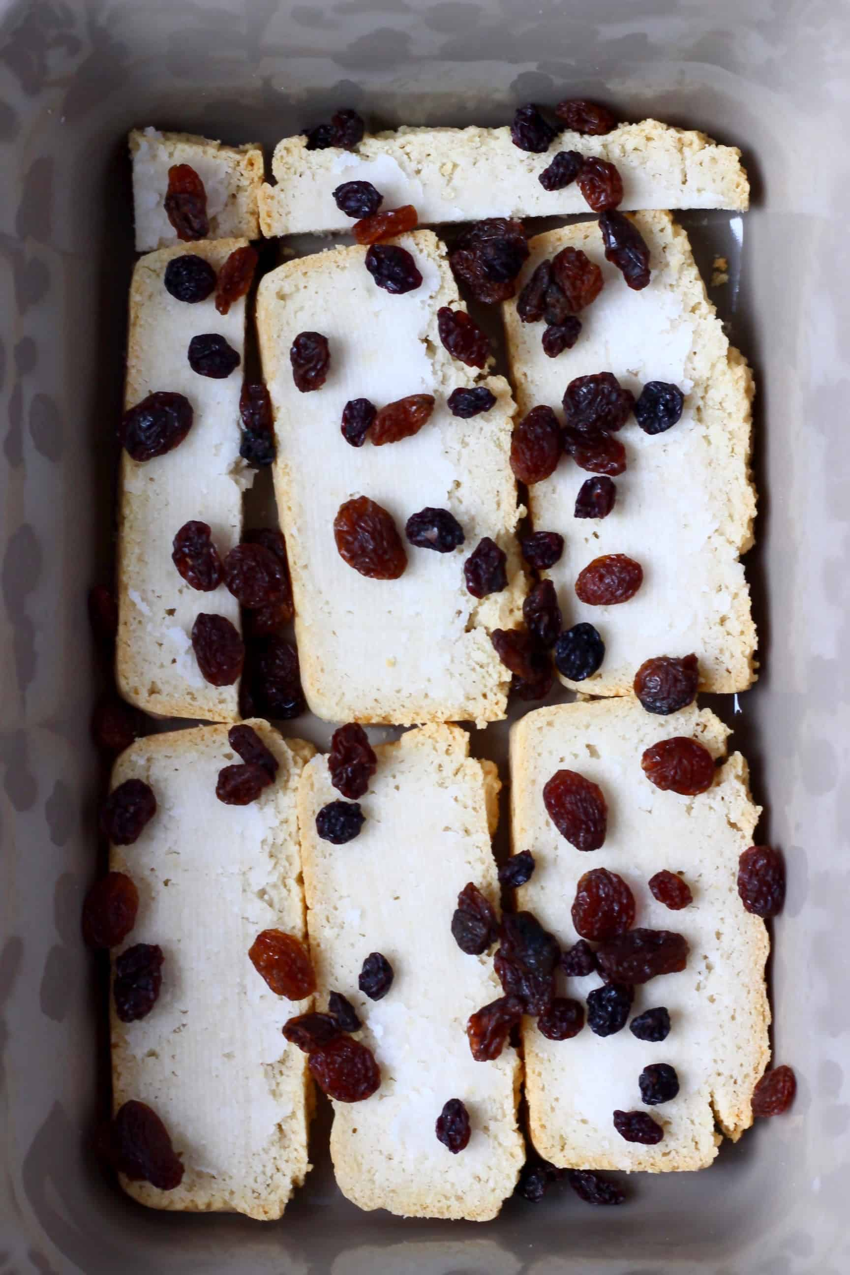Slices of bread spread with coconut oil and topped with raisins in a grey rectangular baking dish