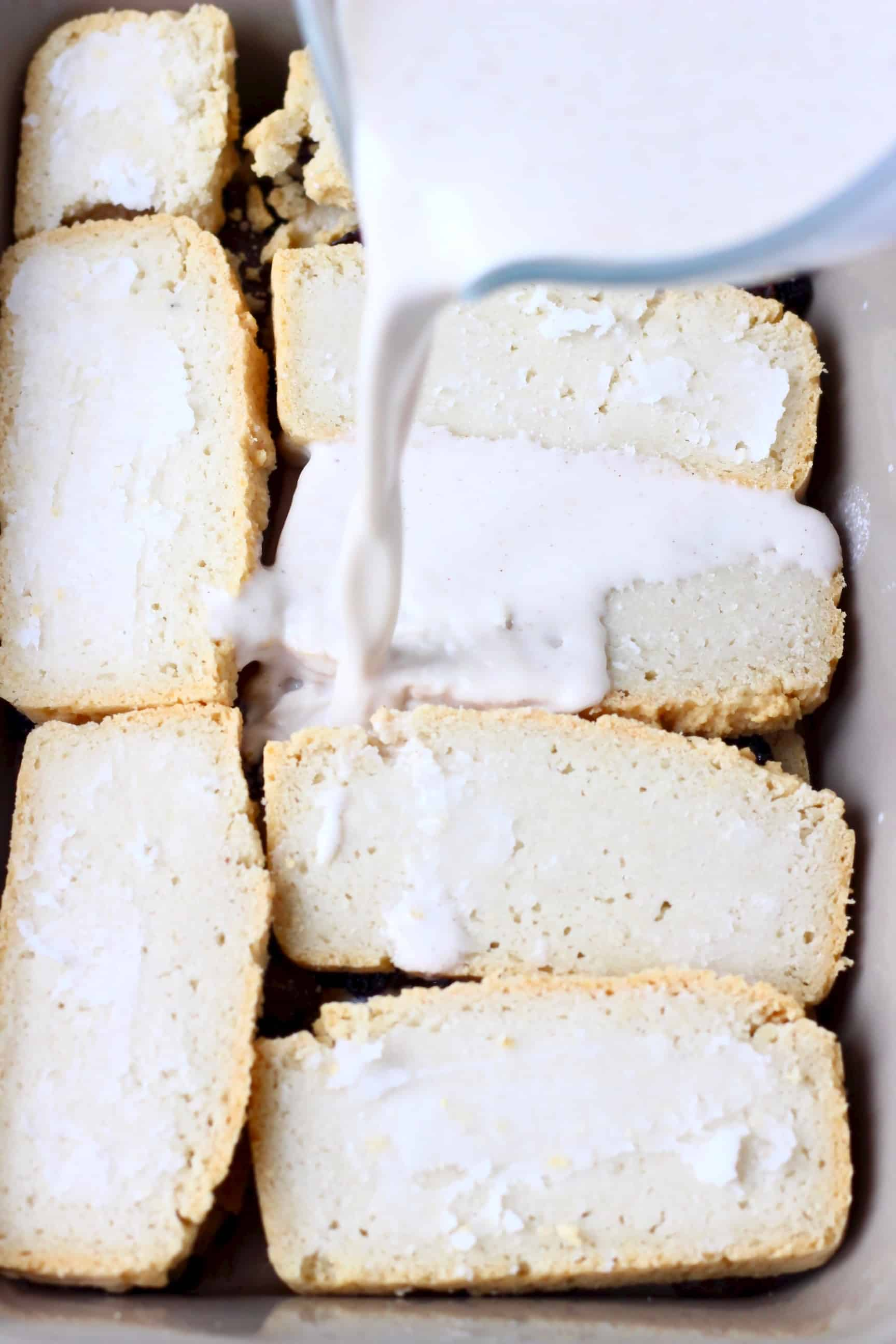 Slices of bread in a grey rectangular baking dish with a white cream being poured over the top with a glass jug