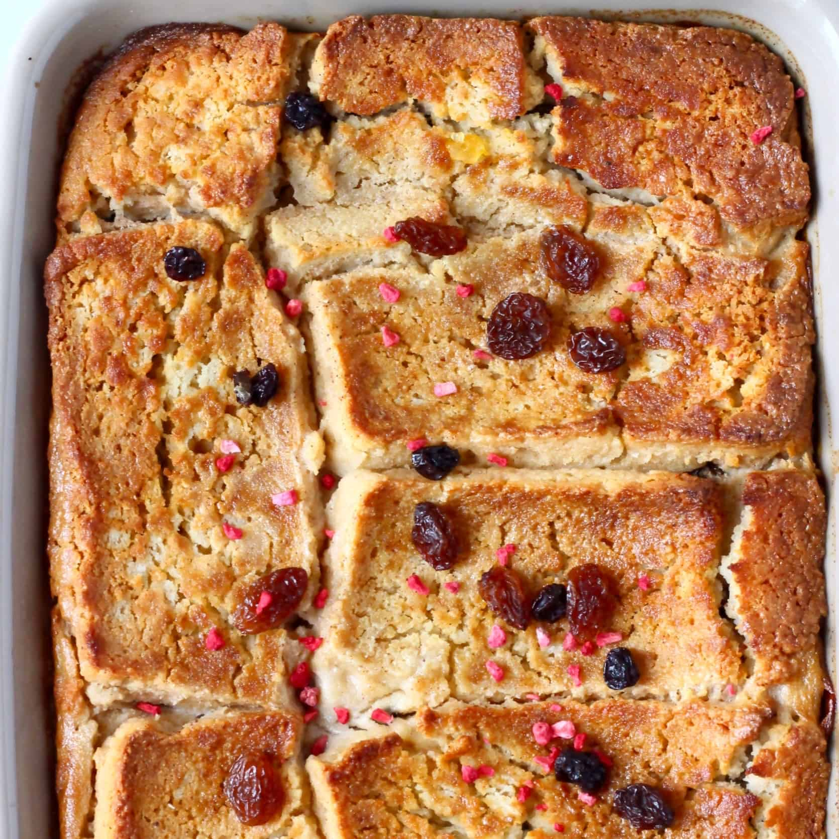 Vegan bread pudding in a grey rectangular baking dish sprinkled with raisins