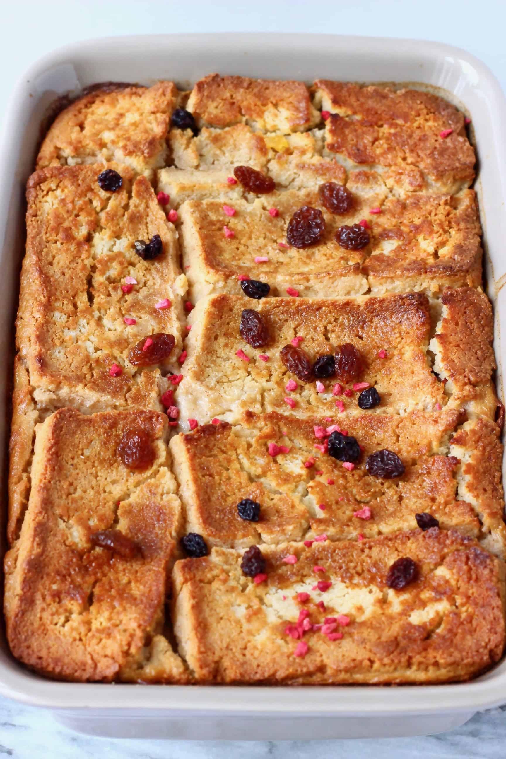 Vegan bread pudding in a grey rectangular baking dish sprinkled with raisins