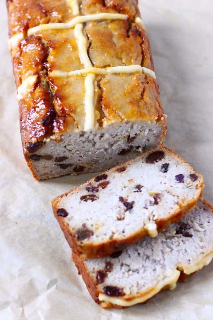 A hot cross bun loaf with two slices next to it against a sheet of brown baking paper