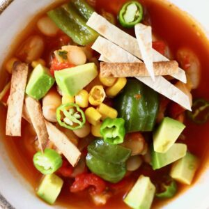 Tomato soup with white beans, sweetcorn and green peppers topped with tortilla strips and diced avocado in a white bowl against a white background