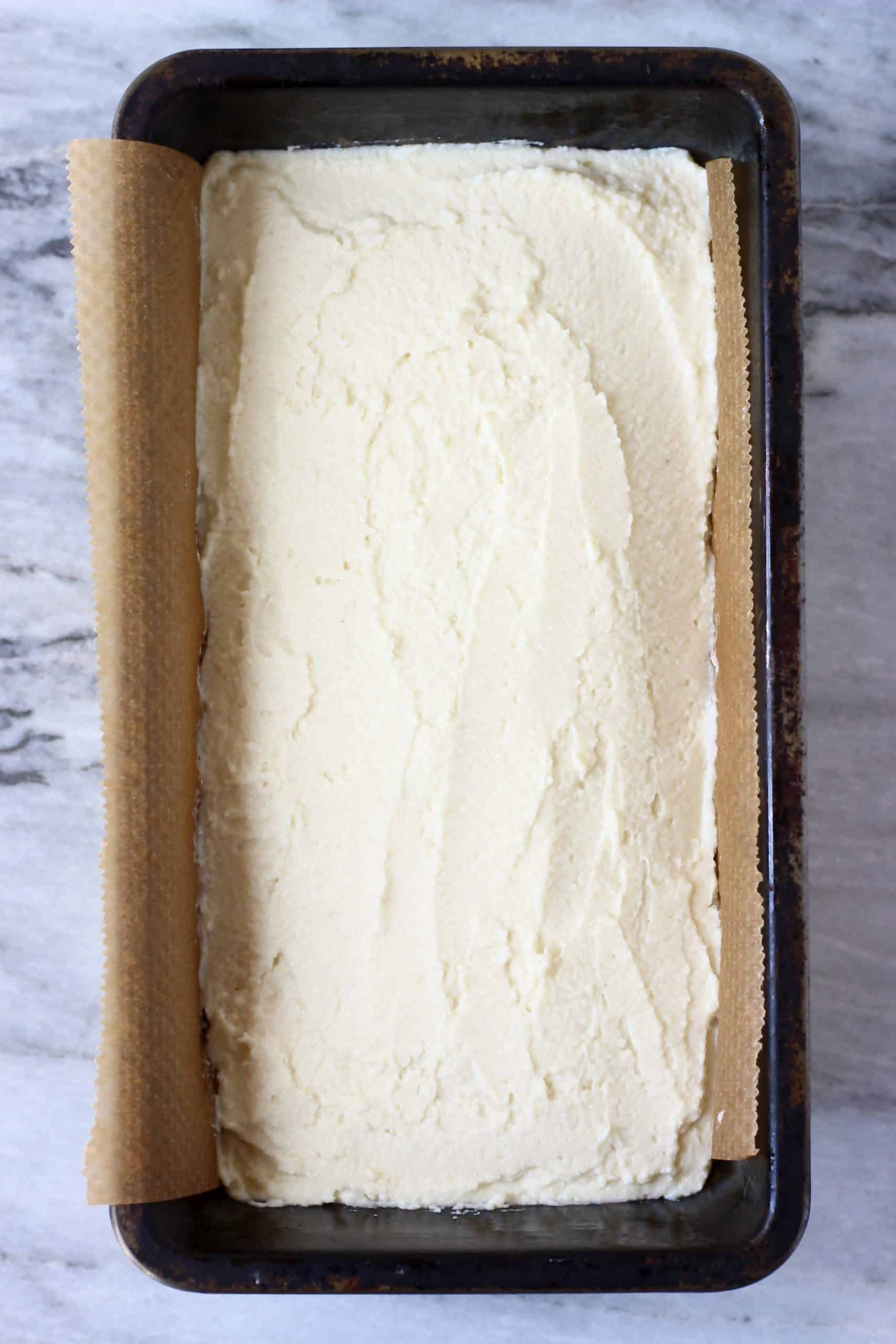 Raw coconut flour bread batter in a loaf tin lined with baking paper