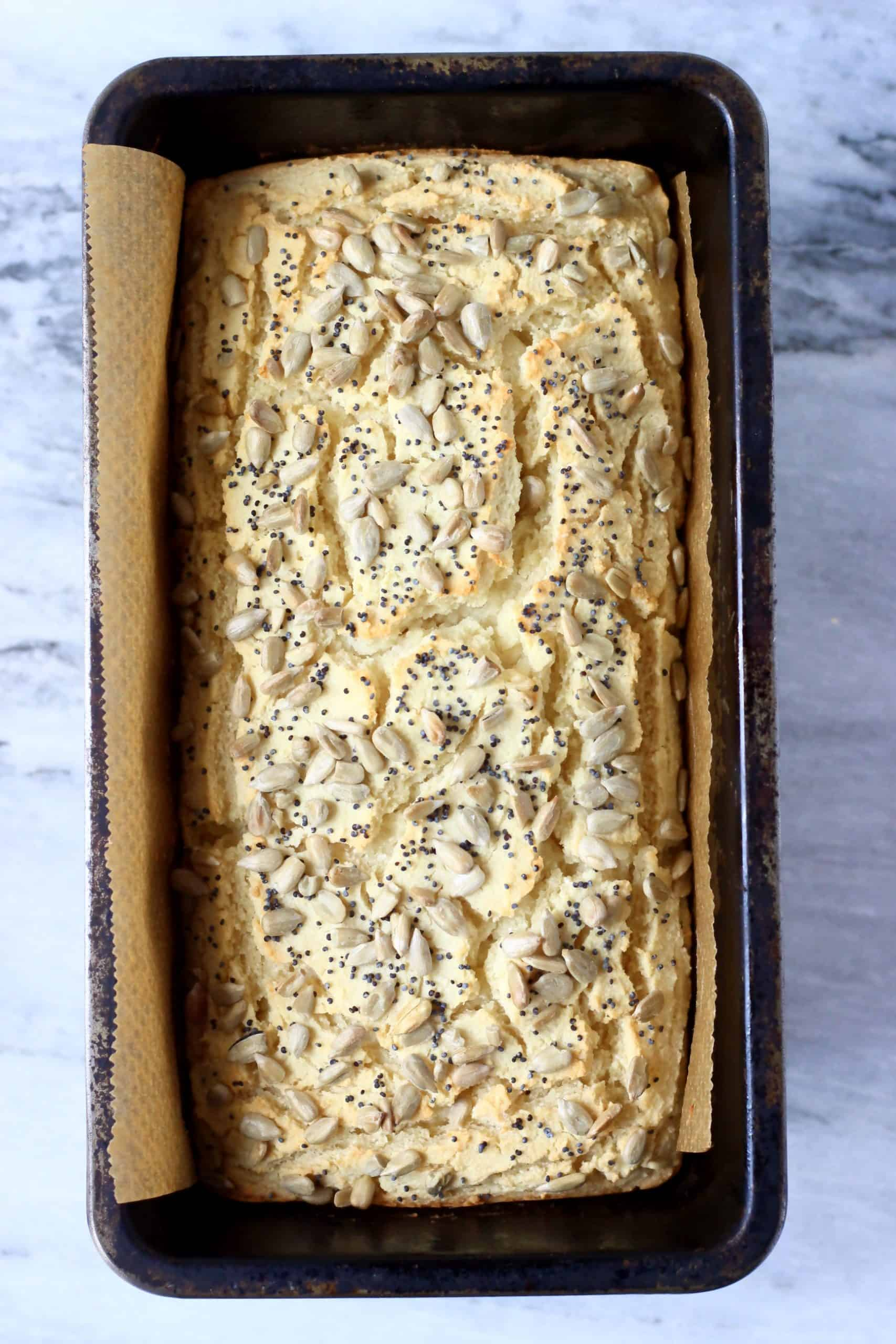 A loaf of coconut flour bread topped with seeds in a loaf tin