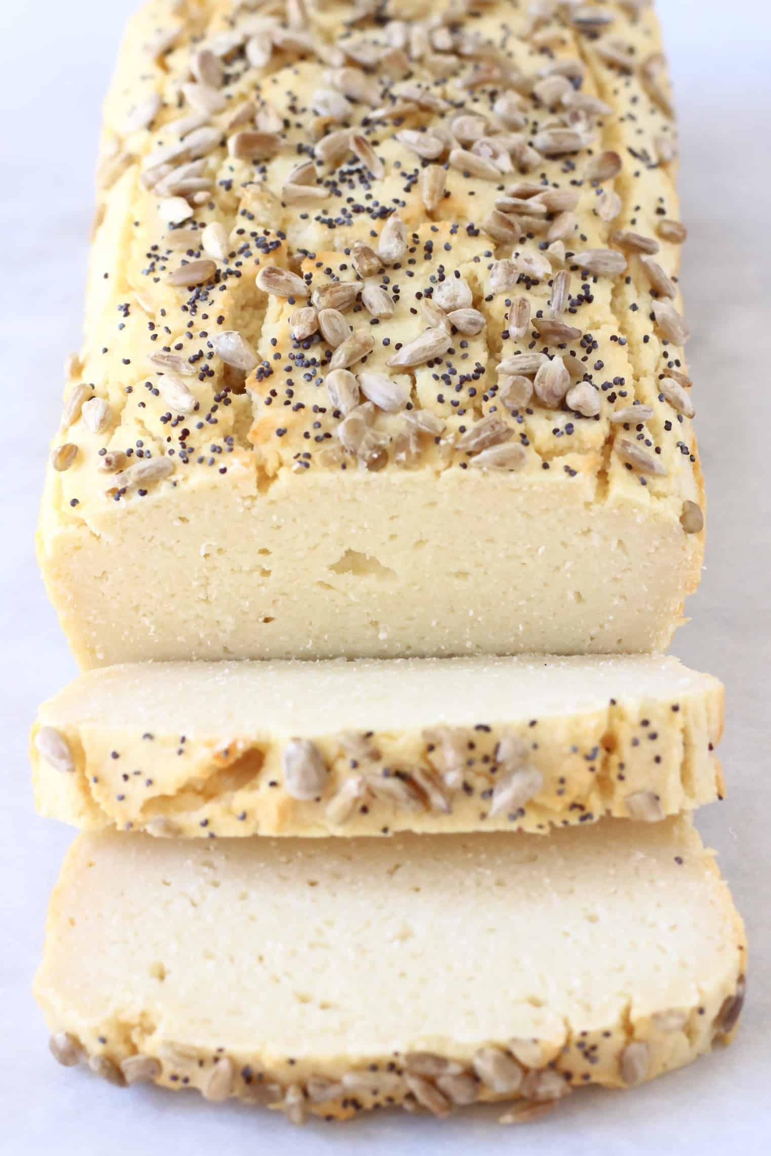 A loaf of coconut flour bread topped with seeds with two slices next to it