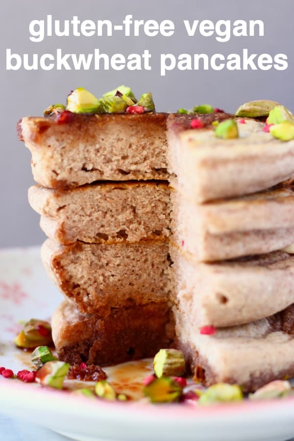 A stack of four buckwheat pancakes on a white plate decorated with chopped pistachios and freeze-dried raspberries covered in dark syrup against a grey background