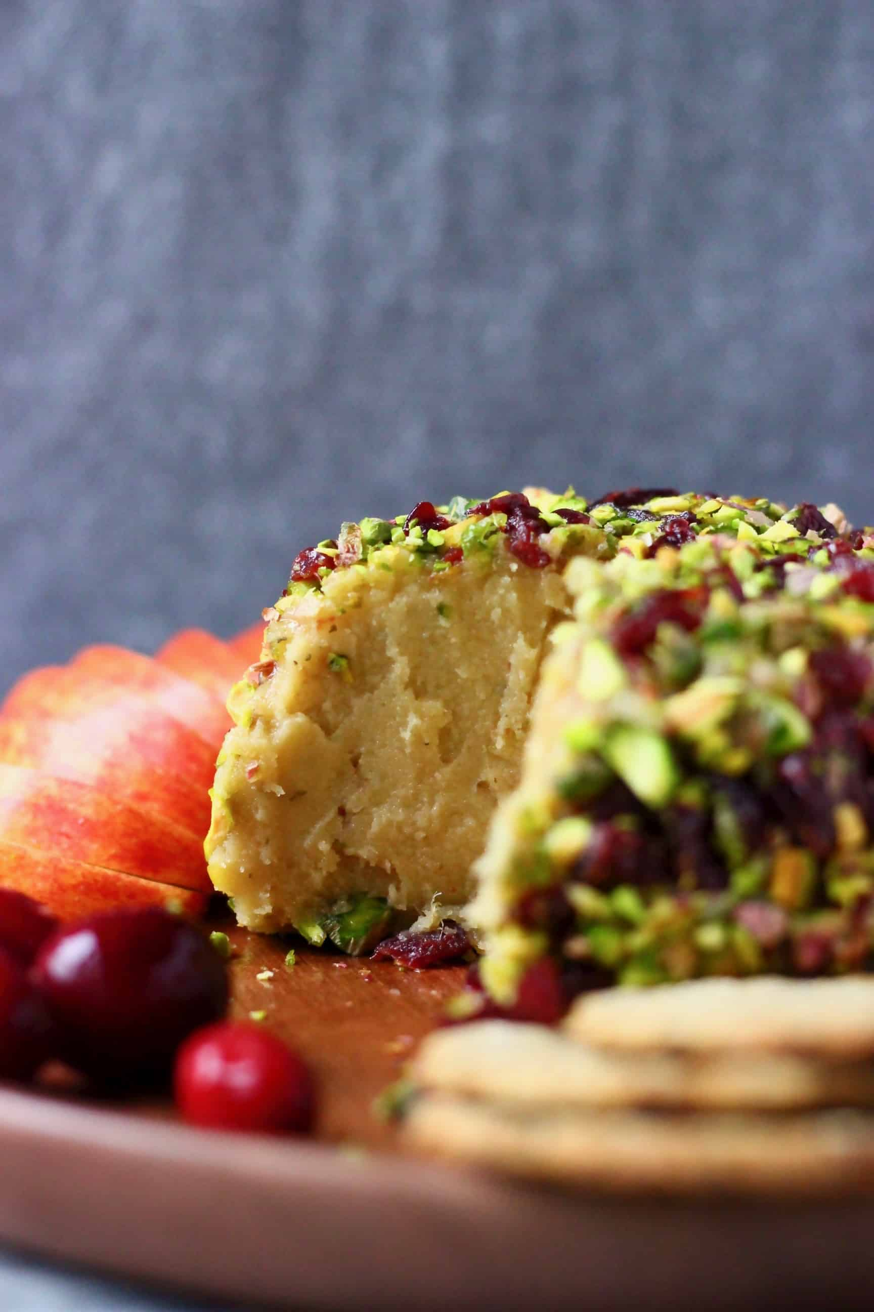 A sliced ball of cashew cheese covered in chopped pistachios and dried cranberries on a wooden plate against a grey background