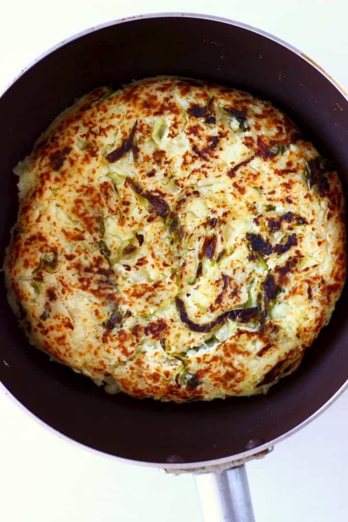 A circular, golden brown bubble and squeak cake in a dark frying pan against a white background