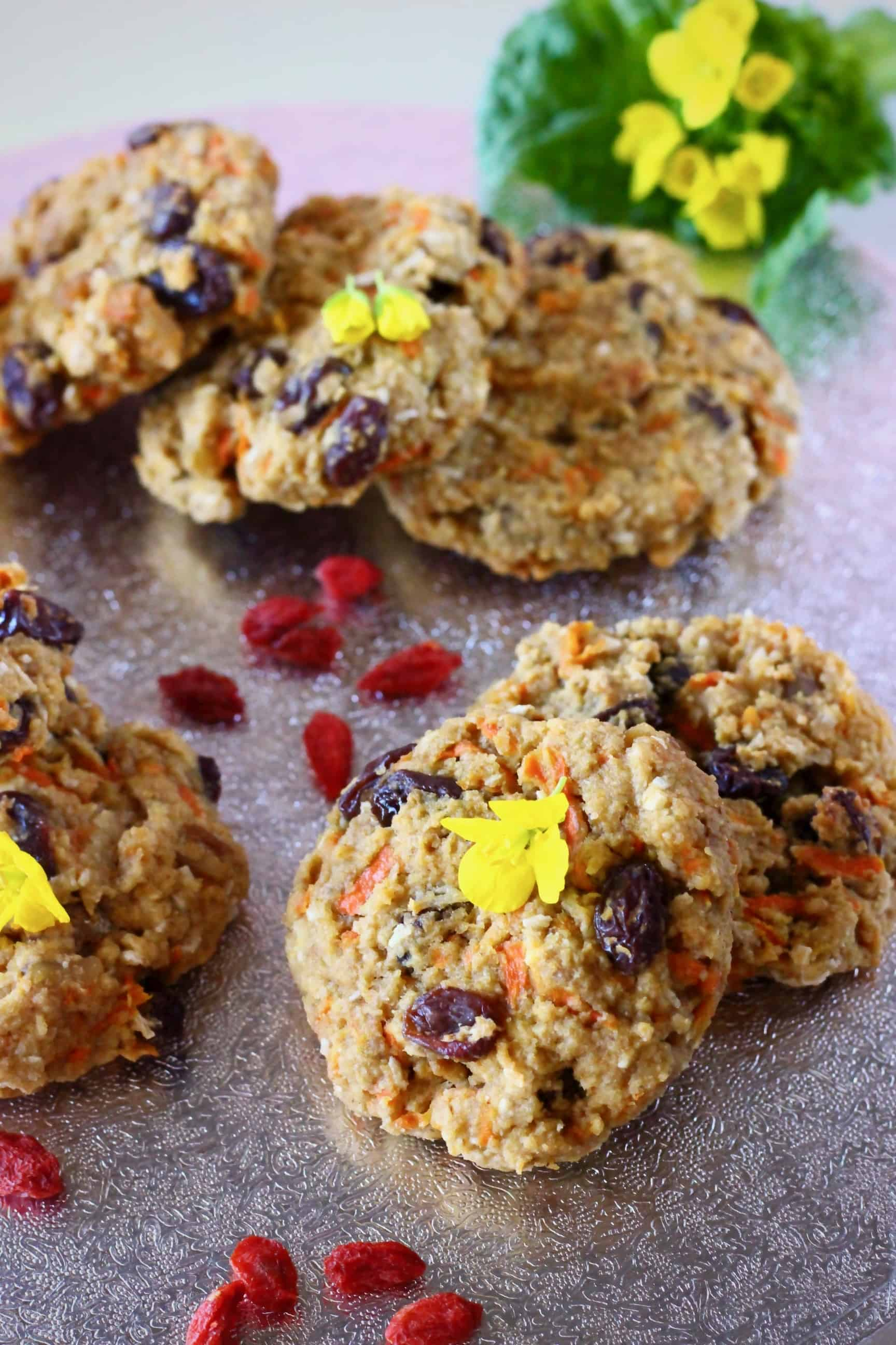 Several carrot cake cookies with raisins on a silver surface sprinkled with goji berries and yellow flowers