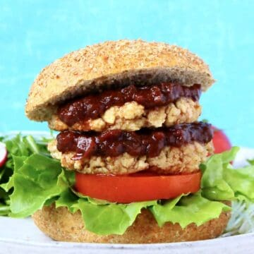 A tofu burger with two patties, brown sauce, lettuce and tomato in a burger bun on a grey plate against a blue background
