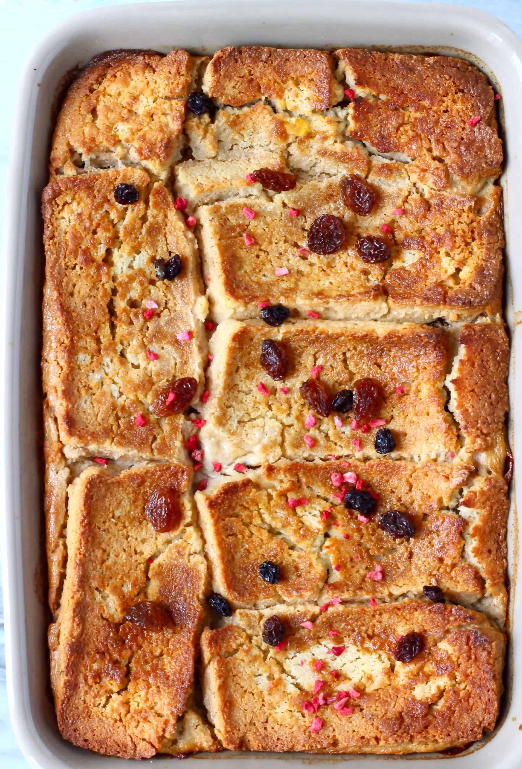 Bread and butter pudding in a grey rectangular baking dish sprinkled with raisins