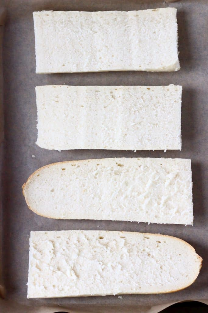 Four pieces of white bread on a sheet of brown baking paper