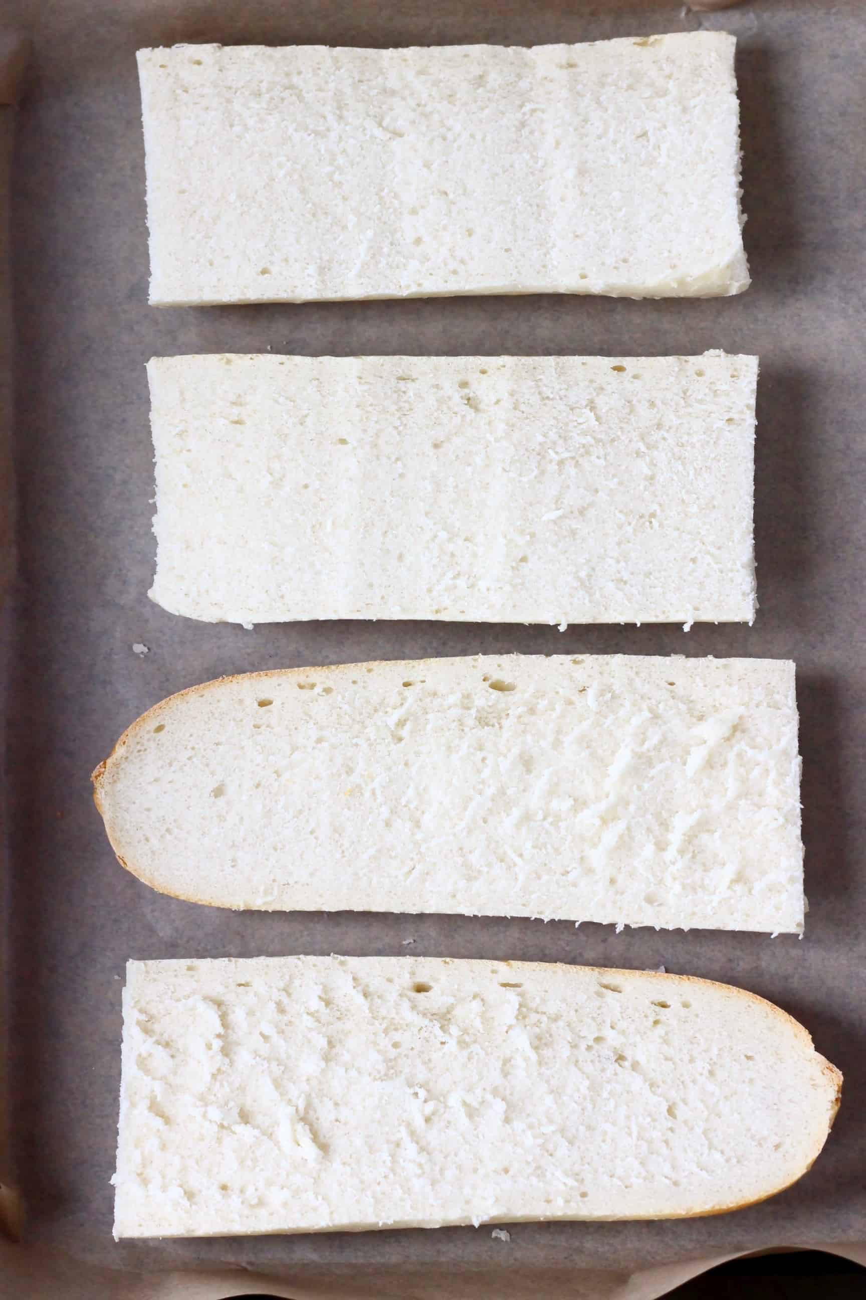 Four pieces of sliced white baguette on a sheet of baking paper