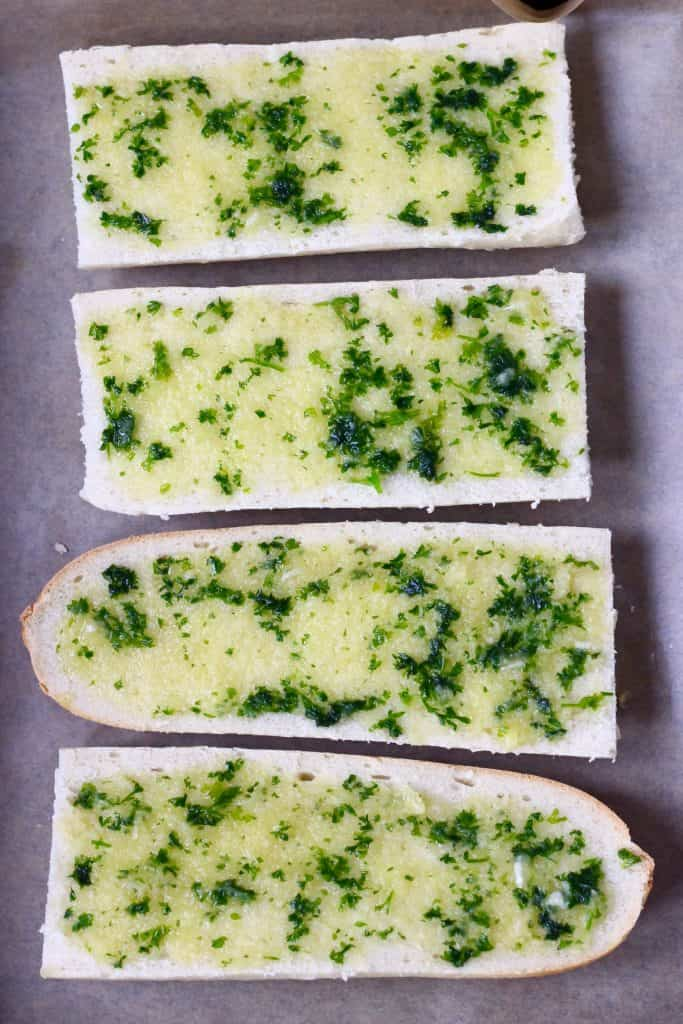 Four pieces of white bread spread with garlic and herb oil on a sheet of brown baking paper