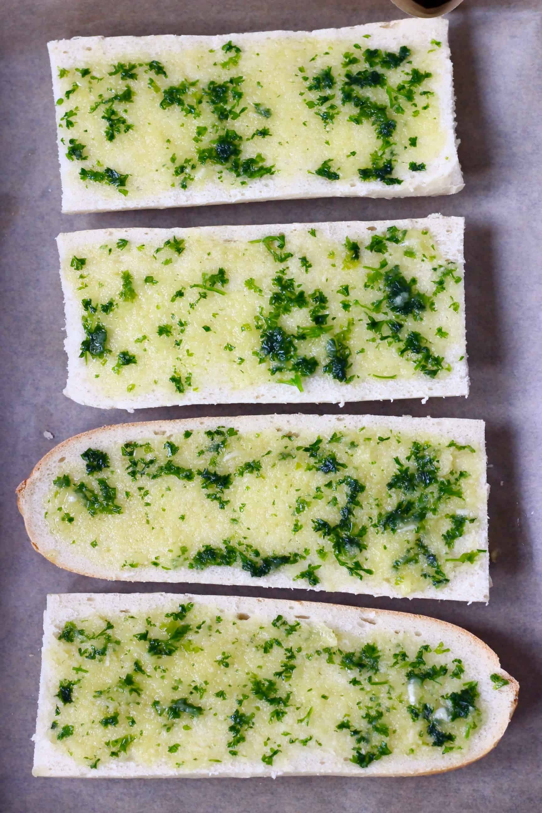 Four pieces of sliced white baguette spread with garlic and herb oil on a sheet of baking paper