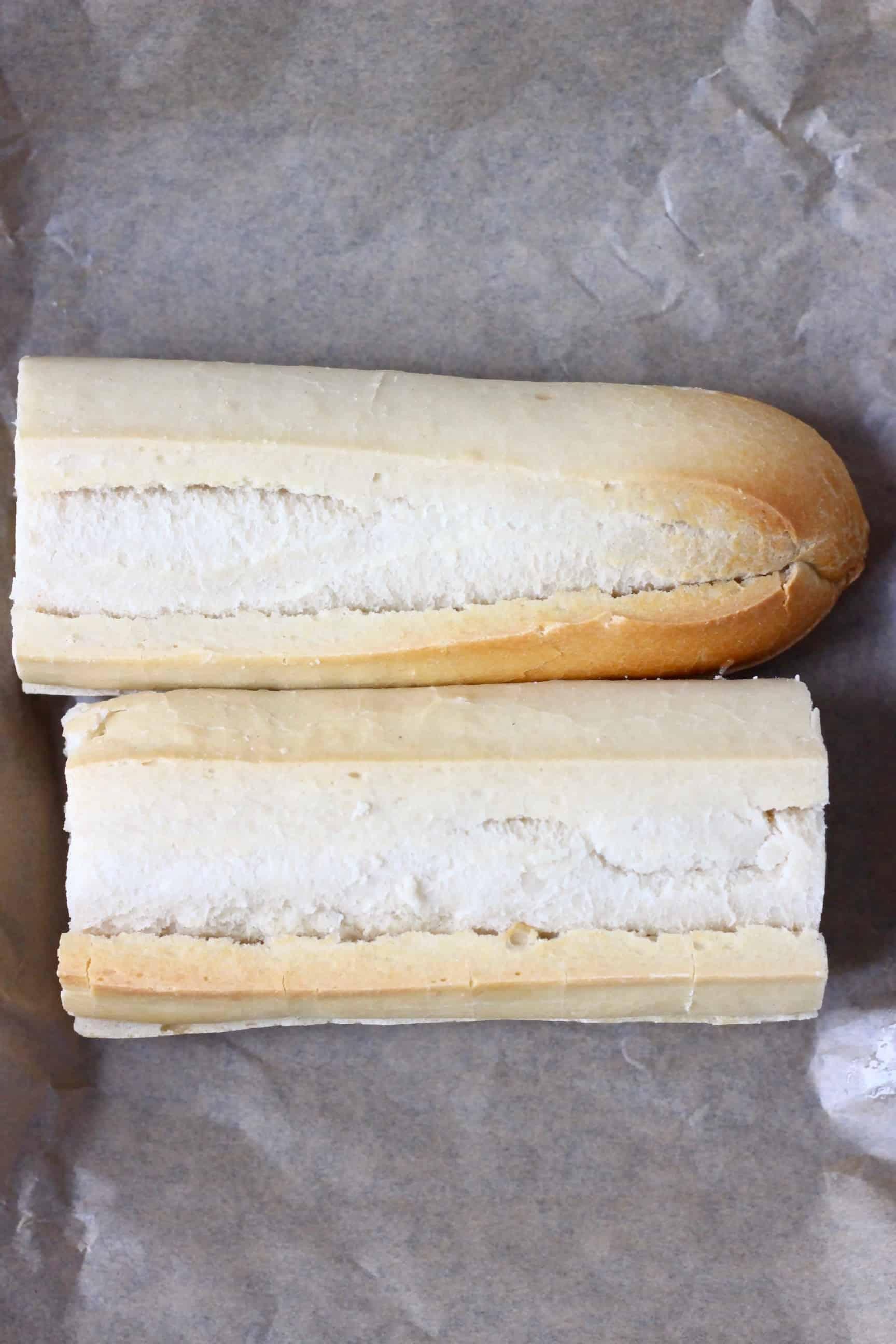 Twi white baguette halves on a sheet of baking paper