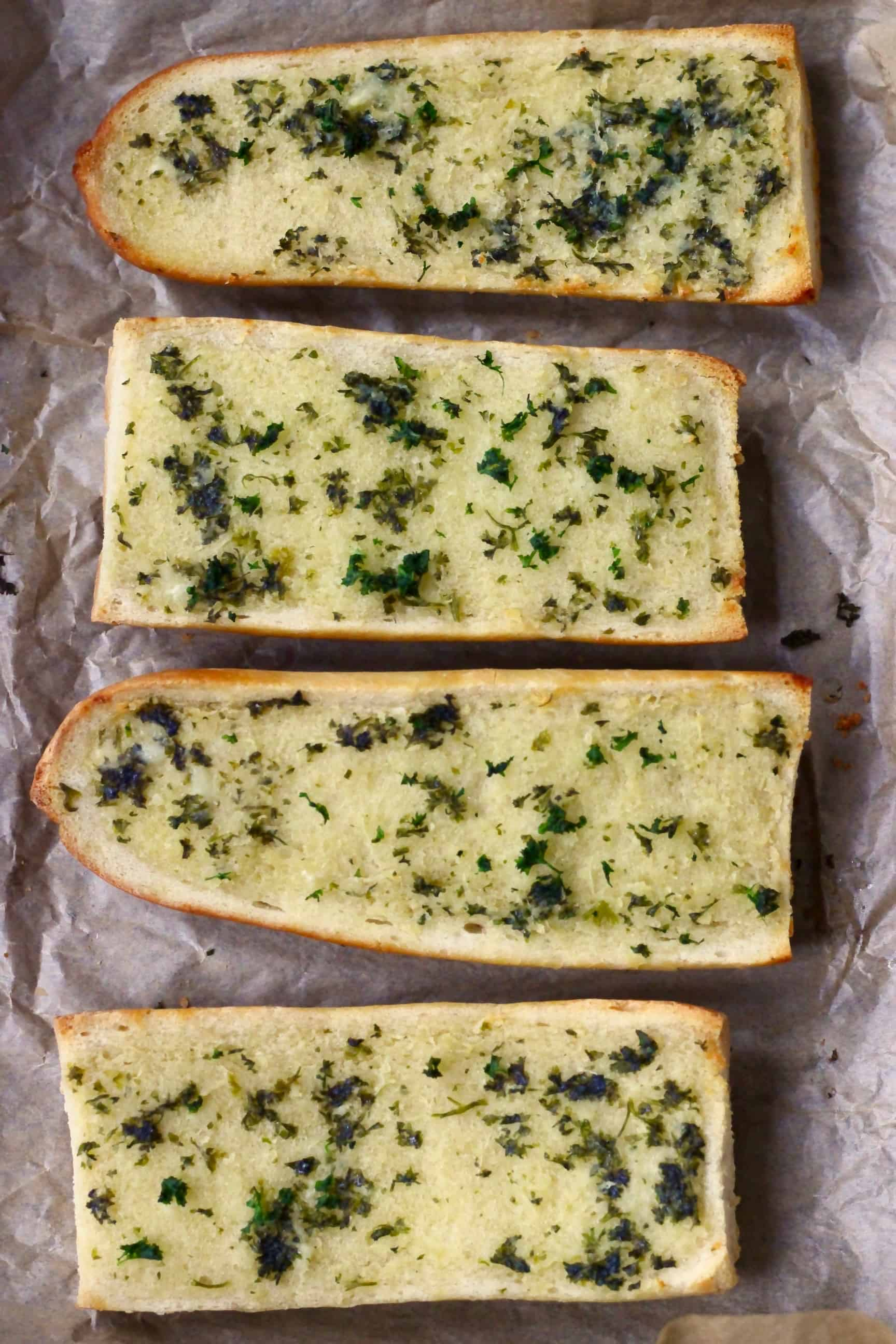 Four pieces of vegan garlic bread on a sheet of baking paper