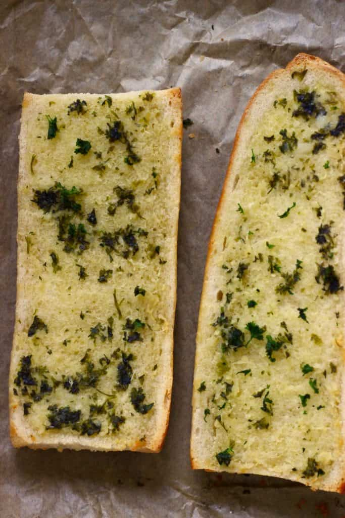 Two pieces of garlic bread on a sheet of brown baking paper