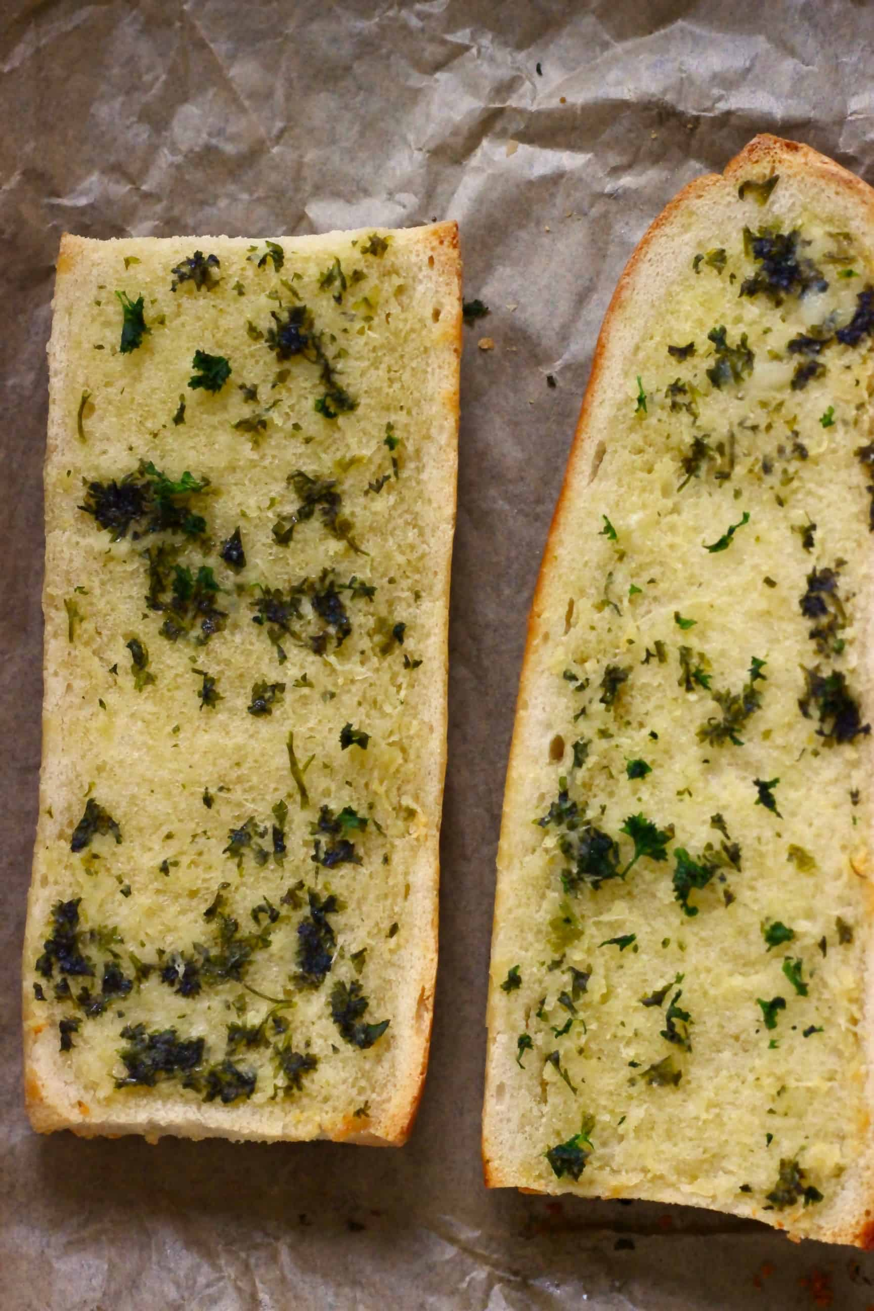 Two pieces of vegan garlic bread on a sheet of baking paper