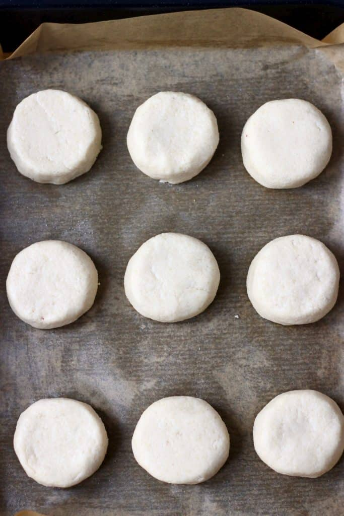 Nine raw scones on a black baking tray lined with brown baking paper