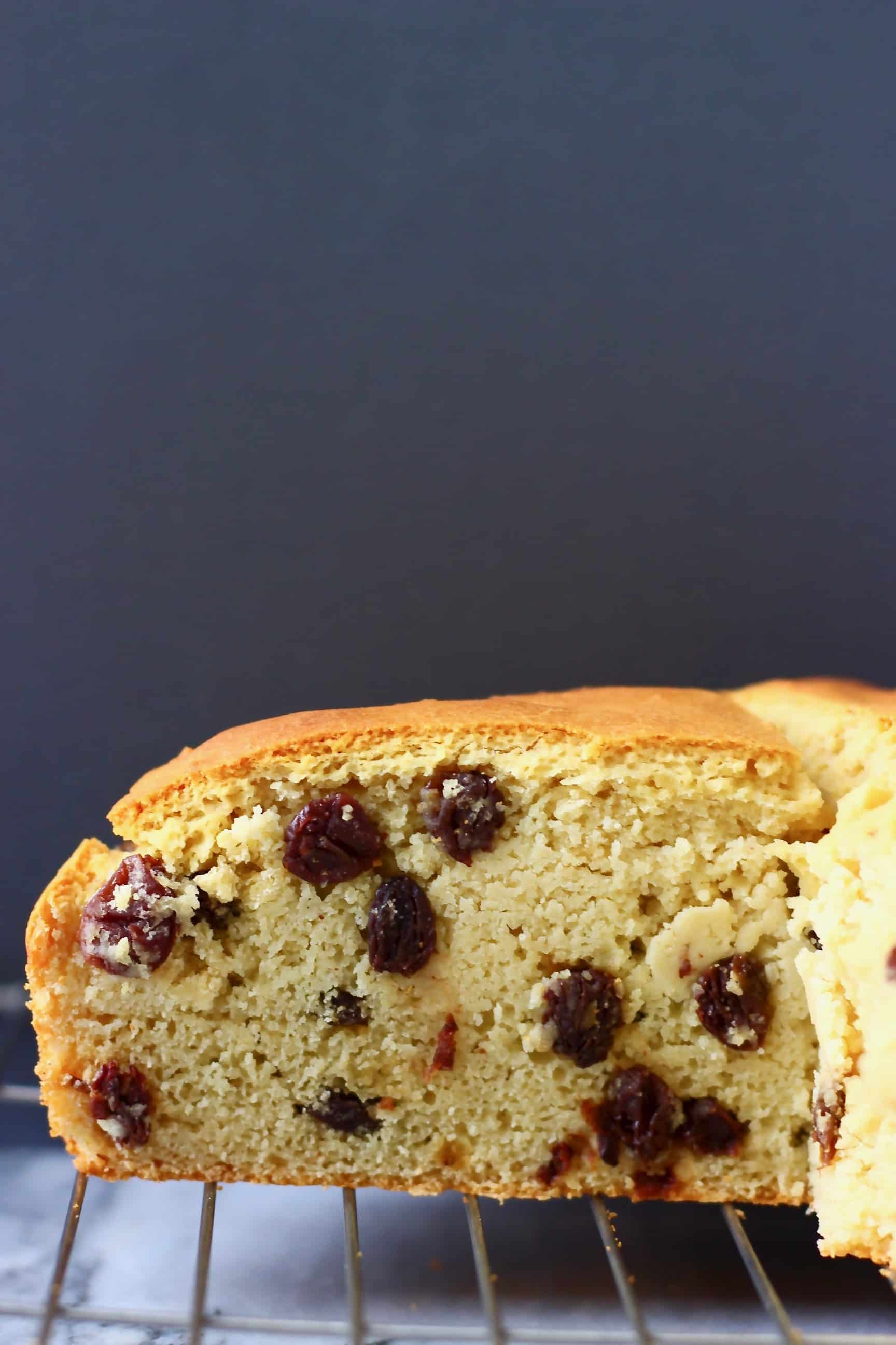A loaf of bread filled with raisins on a wire rack against a dark grey background
