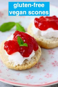 Two scone halves topped with white cream and strawberry jam decorate with mint leaves on a white plate with pink flowers