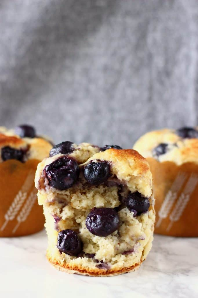 A blueberry muffin with two more muffins in the background on a marble surface against a grey background