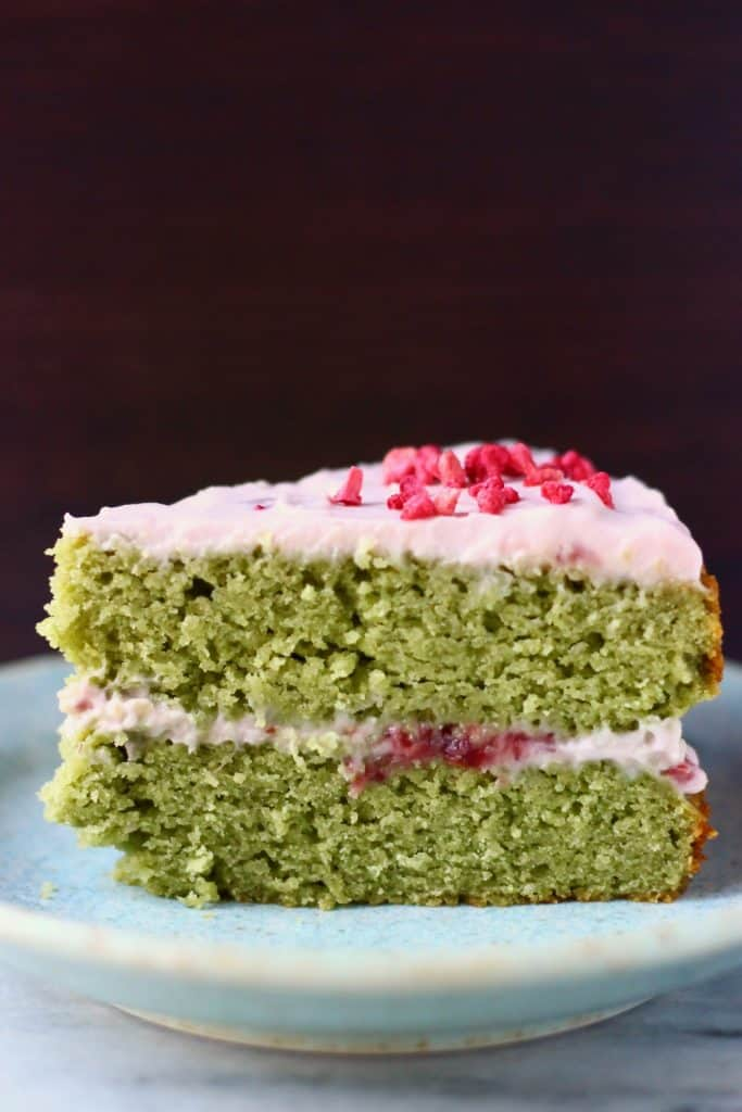 A slice of matcha sponge cake with strawberry frosting on a blue plate against a dark brown background