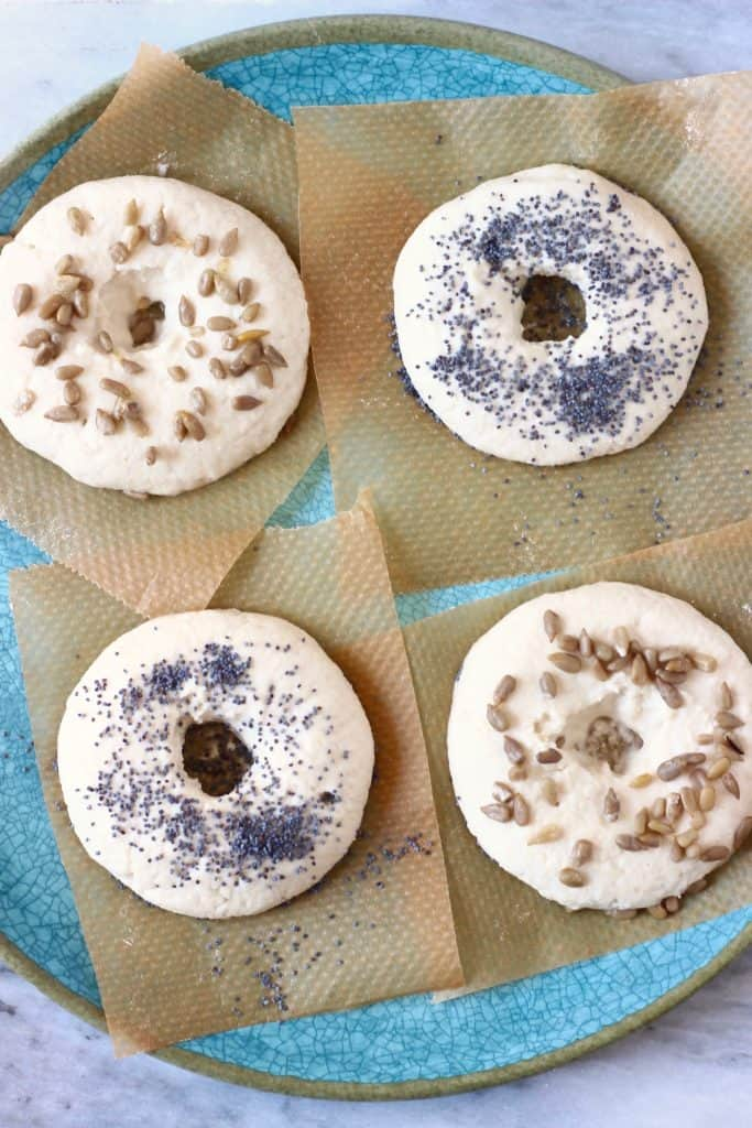 Four raw bagels topped with seeds on pieces of brown baking paper on a blue plate against a marble background
