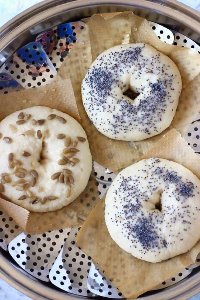 Three raw bagels topped with seeds on pieces of brown baking paper in a silver colander in a silver pan