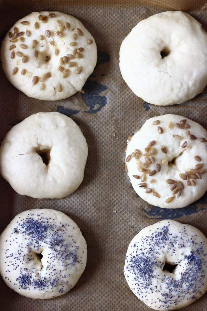 Six bagels topped with seeds on a sheet of brown baking paper