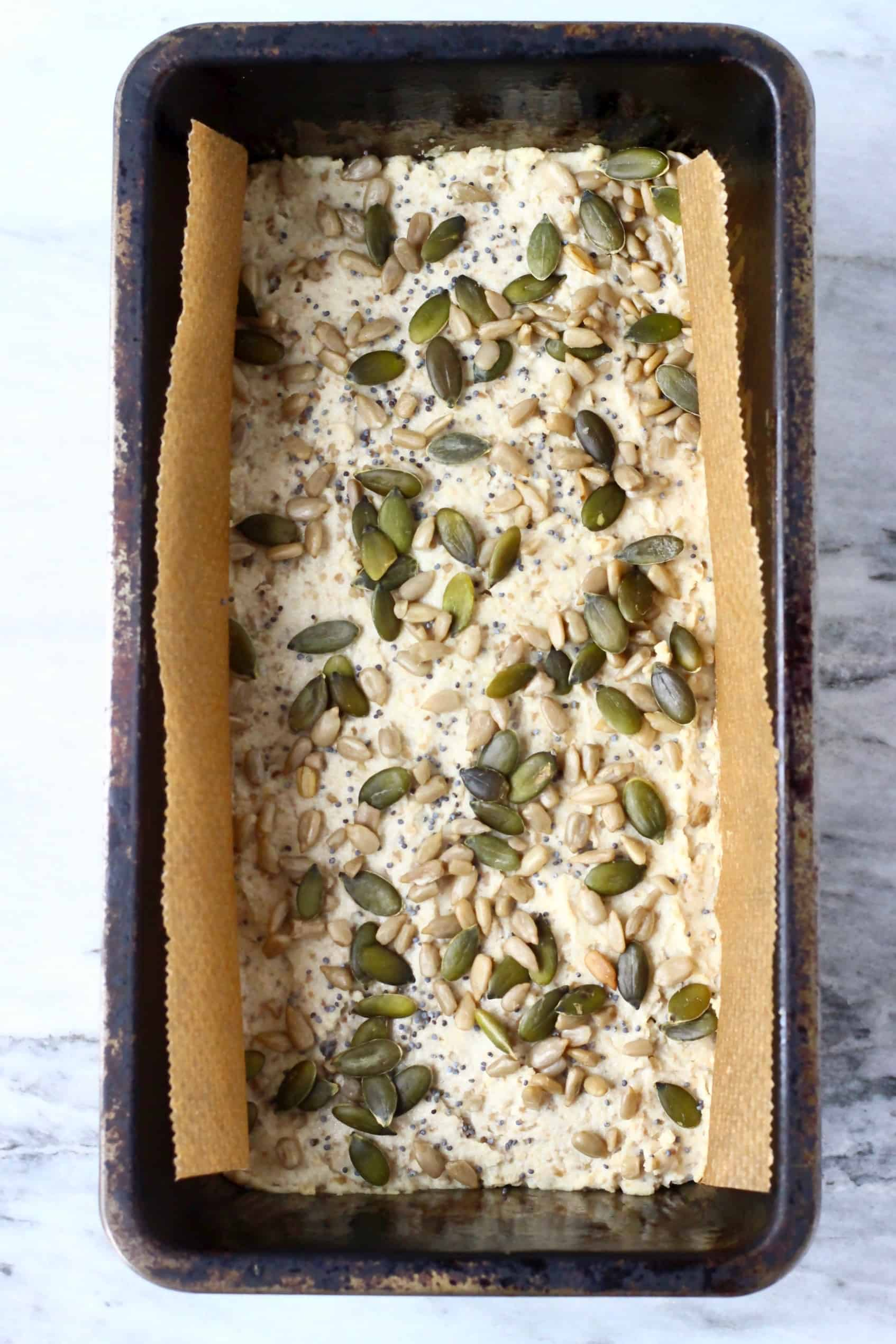 Raw sunflower seed bread batter topped with mixed seeds in a loaf tin lined with baking paper