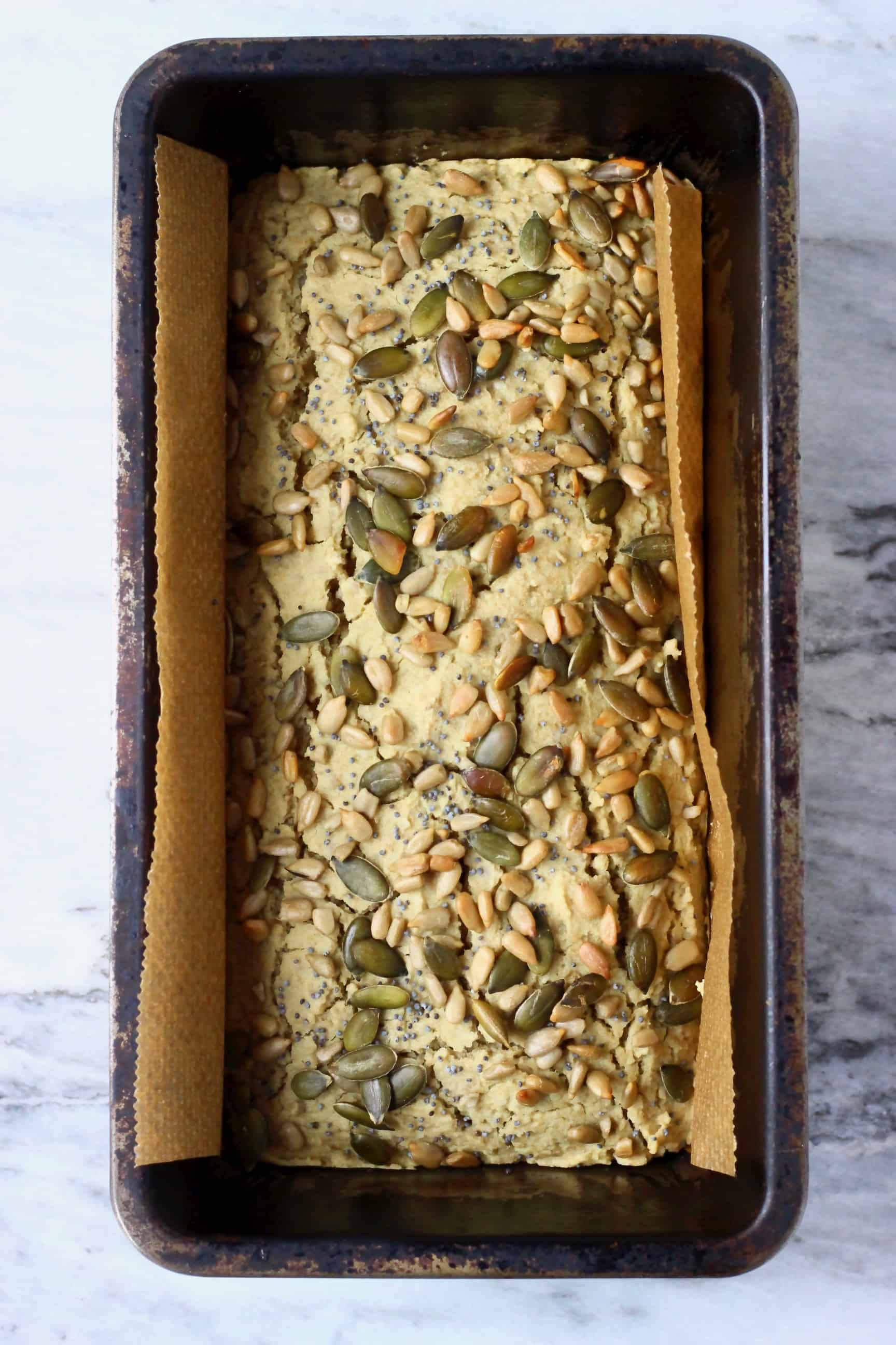 A loaf of sunflower seed bread topped with mixed seeds in a loaf tin