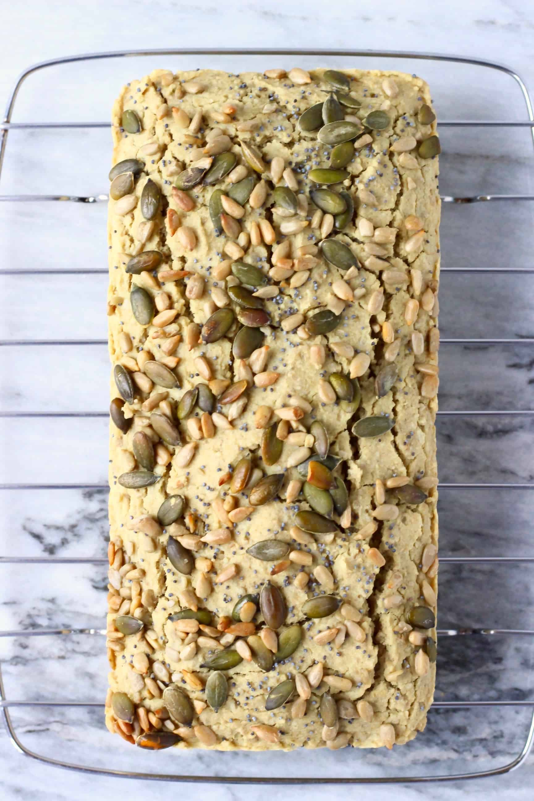 A loaf of sunflower seed bread topped with mixed seeds on a cooling rack