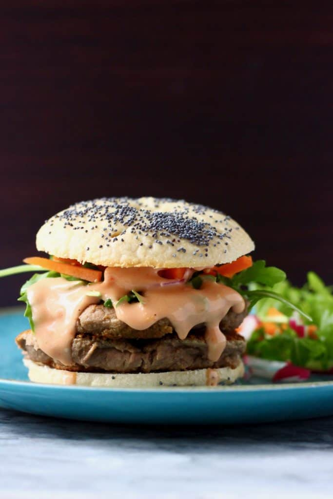 A bagel burger with vegan sausage patties, pink sauce and salad on a blue plate against a dark brown background
