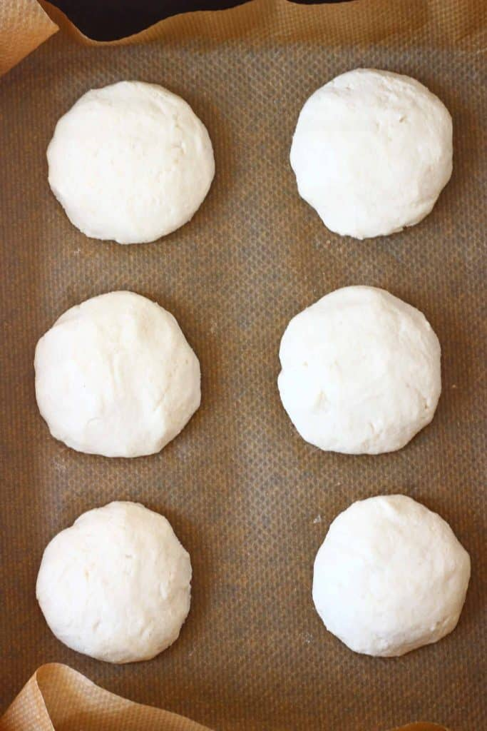 Six raw bread rolls on a sheet of brown baking paper