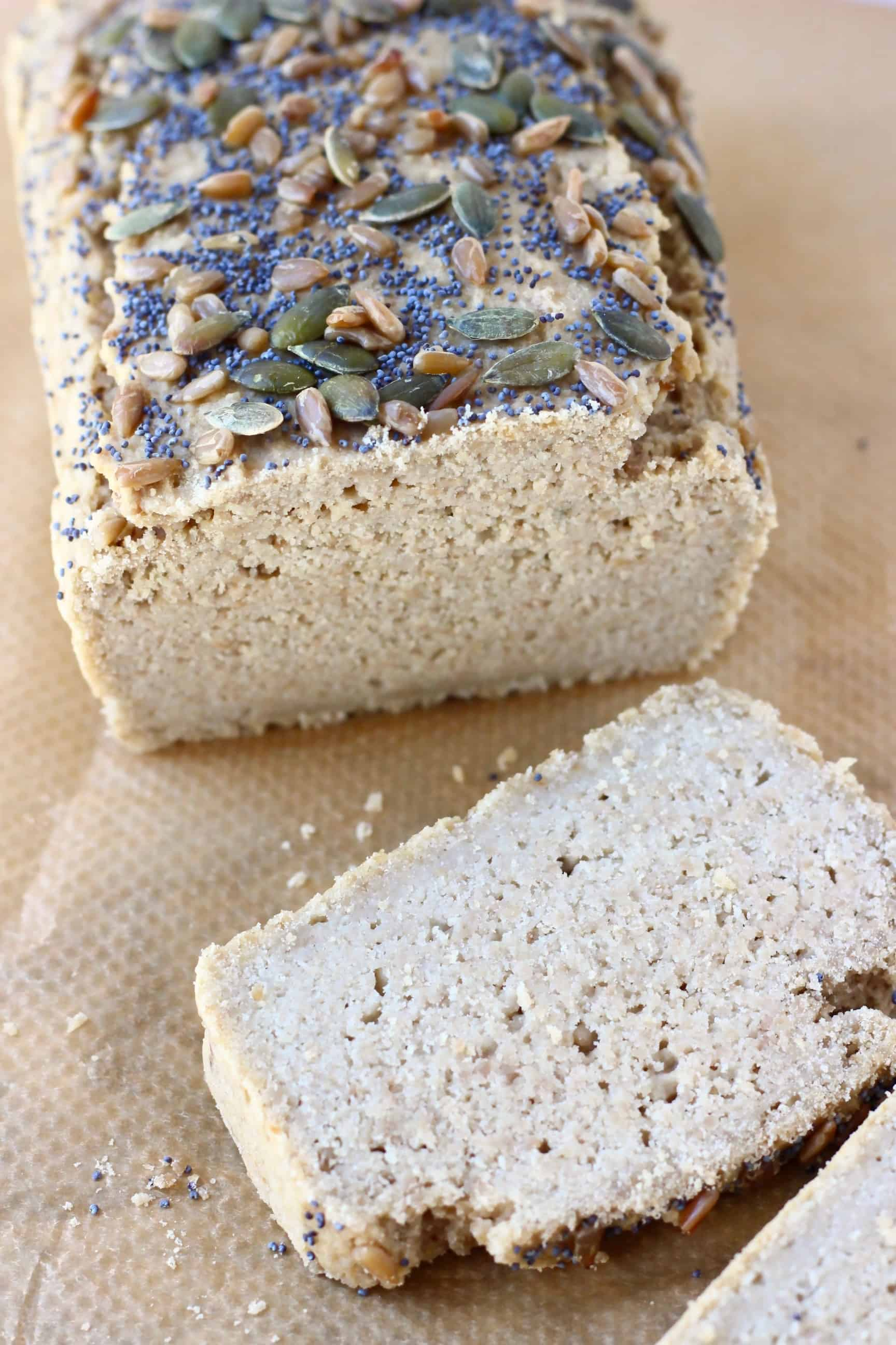 A loaf of sunflower seed bread topped with mixed seeds with two slices of bread next to it