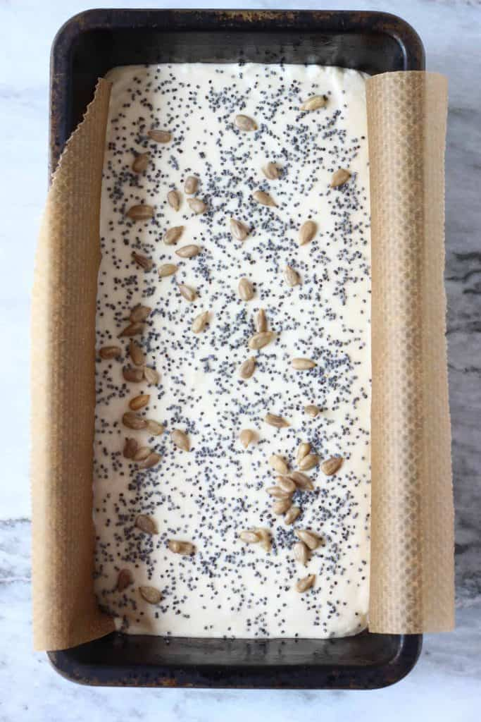 White bread dough topped with mixed seeds in a black loaf tin lined with baking paper against a marble background