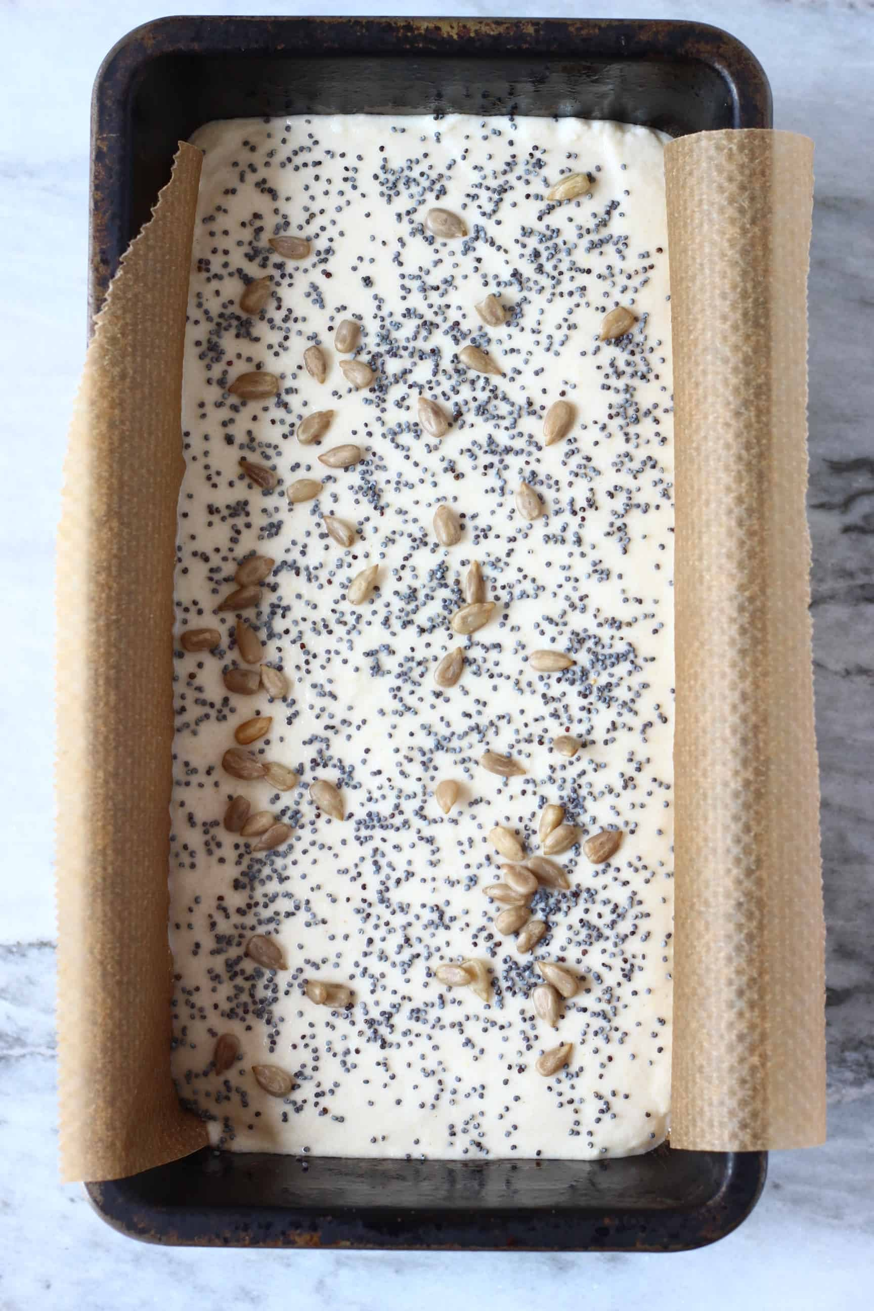 White gluten-free rice bread batter topped with seeds in a black loaf tin lined with baking paper