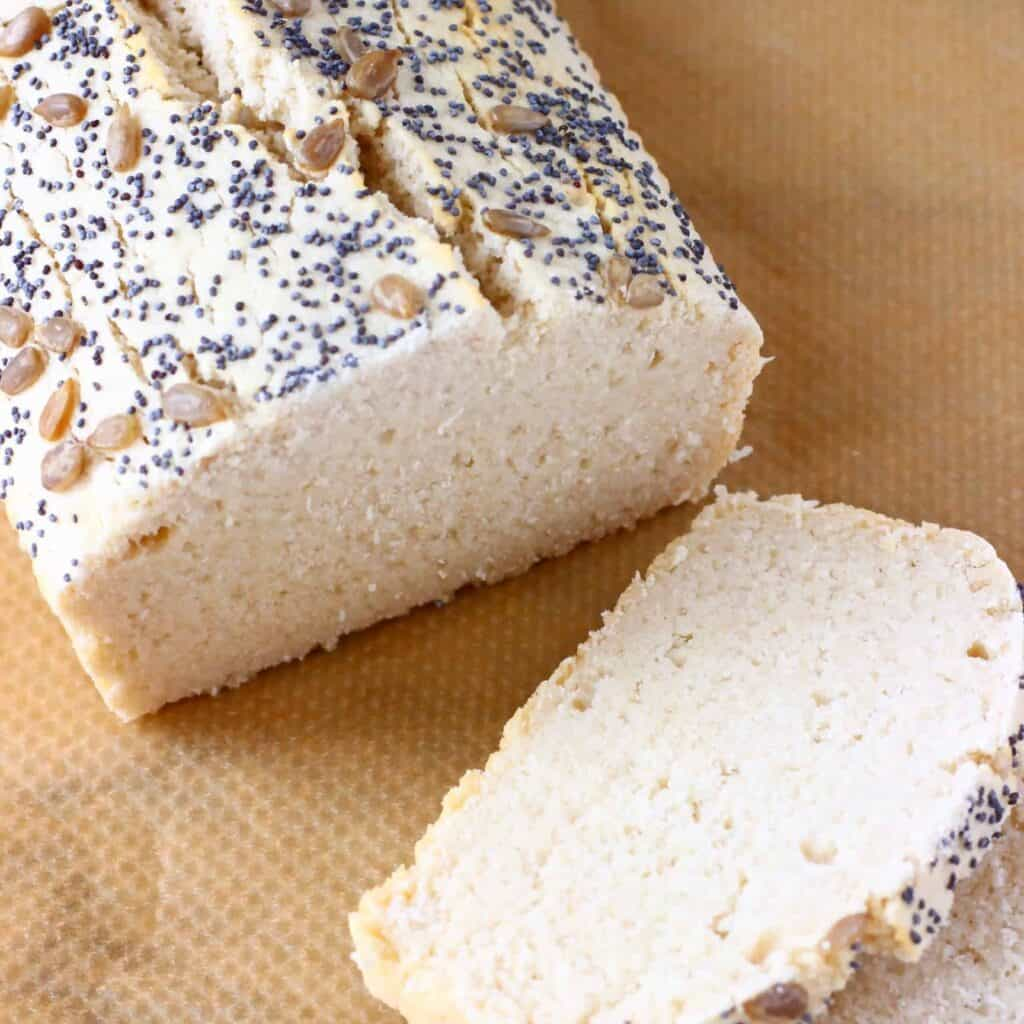 A loaf of white bread topped with mixed seeds with two slices next to it against a sheet of brown baking paper