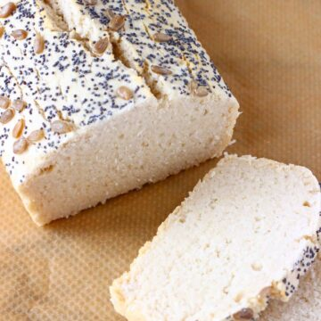 A loaf of gluten-free rice bread topped with mixed seeds with two slices next to it against a sheet of brown baking paper