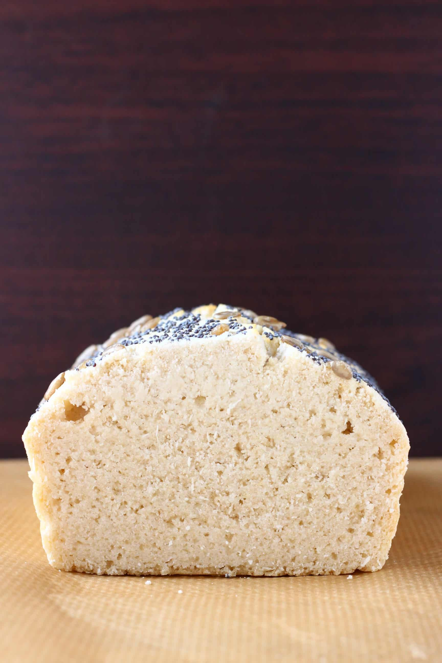 A sliced loaf of gluten-free rice bread on a sheet of brown baking paper