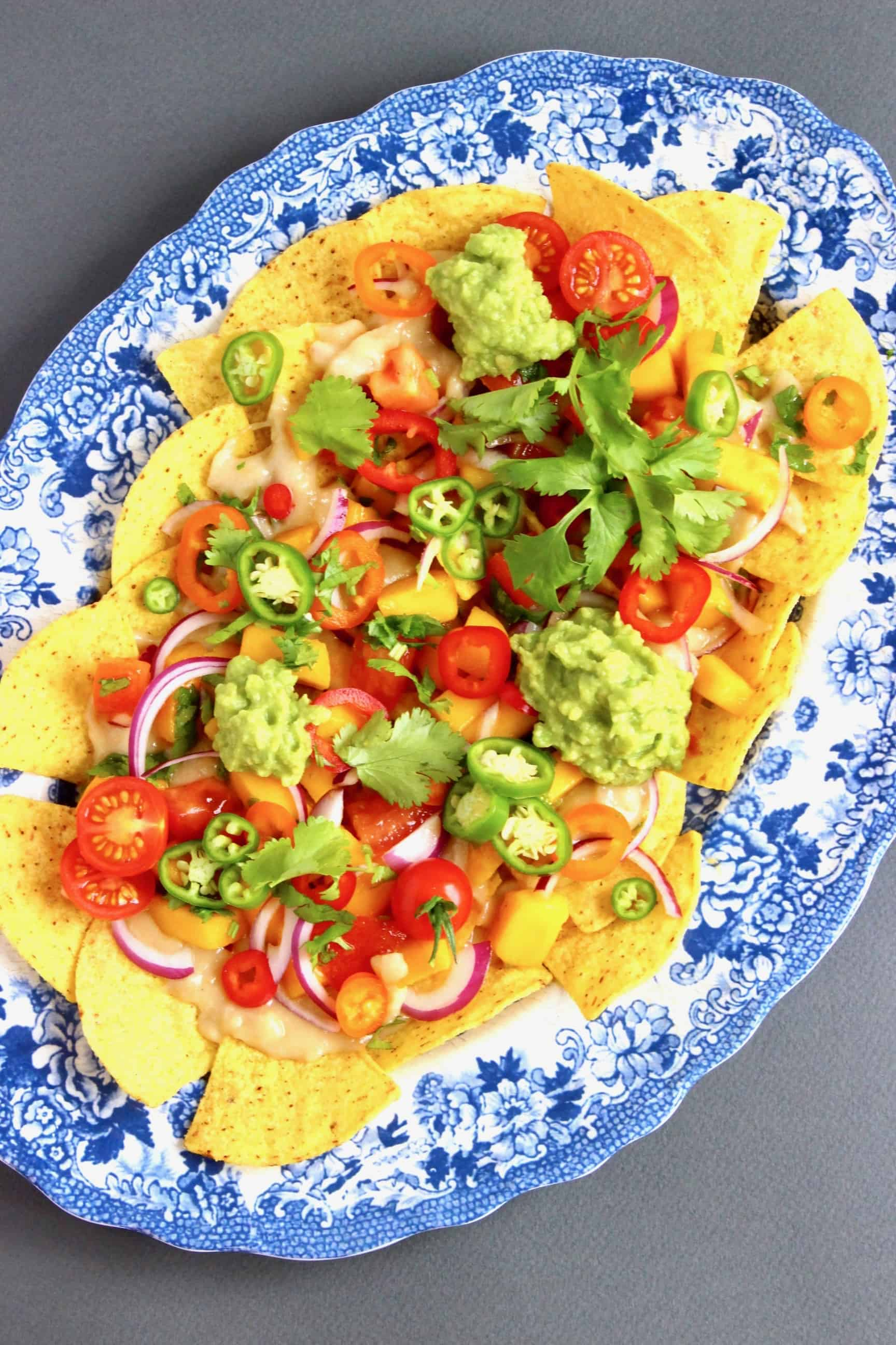 Nachos topped with lots of different vegetables on a oval blue plate against a grey background