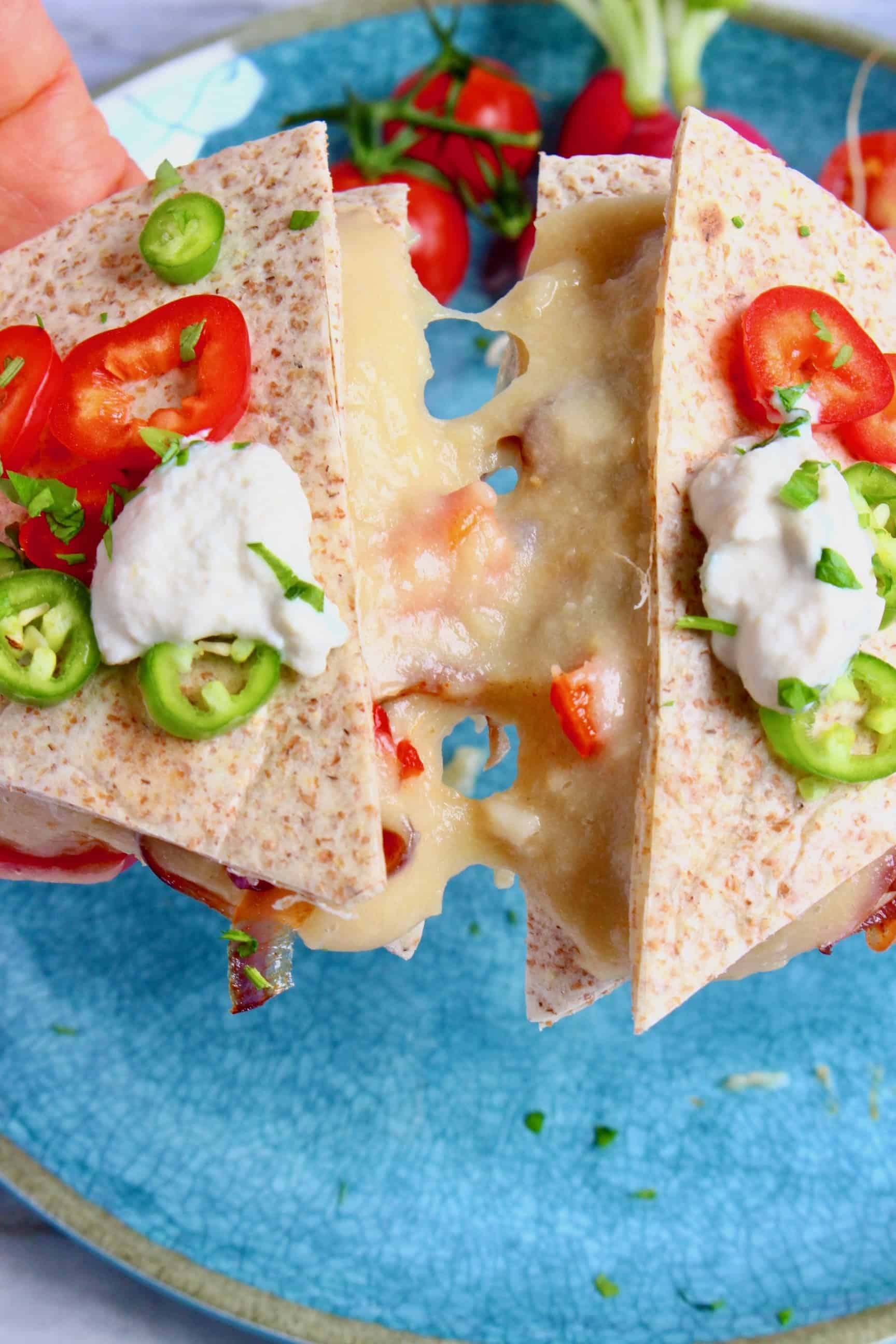 A quesadilla with cheese and vegetables being held up against a blue plate