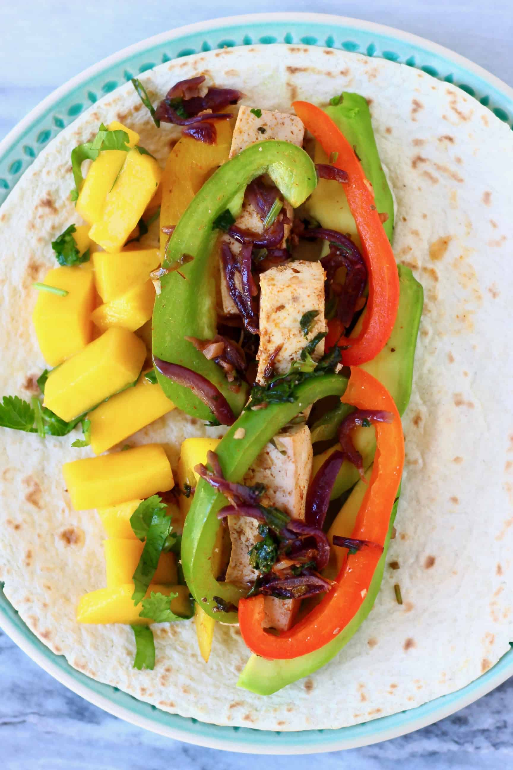 Photo of tofu, sliced peppers and diced mango on a tortilla on a blue plate